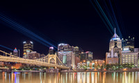 Lasers shine across the river and display the Bat symbole on downtown Pittsburgh