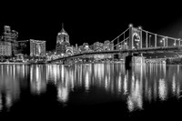 Black and white view of the Clemente Bridge and Bat Signal in Pittsburgh