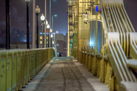 A lone person walks on the snow covered Clemente Bridge in Pittsburgh