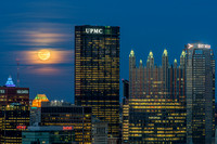 The rising full moon sits behind the clouds in Pittsburgh