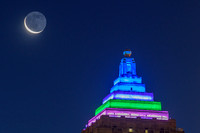 A sliver of moon by the colorful Gulf Tower in PIttsburgh
