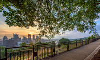 Trees frame the Pittsburgh skyline and Grandview Avenue at dawn