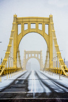 The snowy Clemente Bridge leads into a squall in Pittsburgh