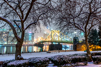 A beautiful winter scene on the North Shore of Pittsburgh, as trees frame the Clemente Bridge