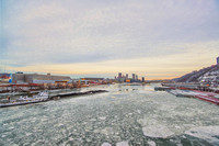 Wide angle barge on the icy Ohio River with the Pittsburgh skyline in the background