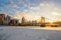 Sun through the Roberto Clemente Bridge with the Allegheny River covered in ice