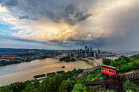 Rain showers move through Pittsburgh as a small rainbow forms over the city