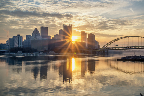 Sun burst through the middle of downtown Pittsburgh at dawn