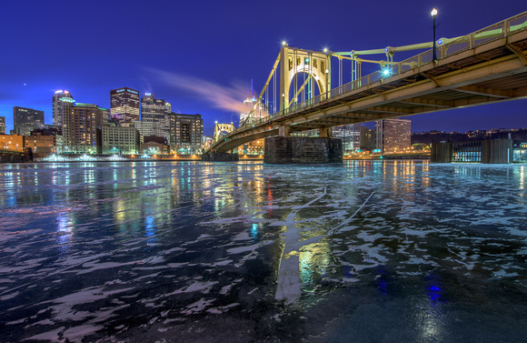 The Roberto Clemente Bridge reflects int he icy Allegheny