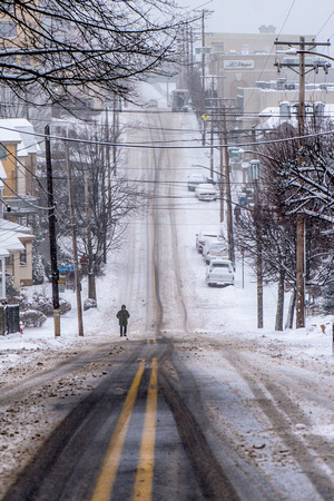 A lone man walks the snow covered streets of Mt. Washington in Pittsburgh