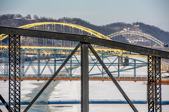 Bridges in Pittsburgh over snowy rivers