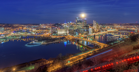 Light streaks from the incline and a full moon over Pittsburgh