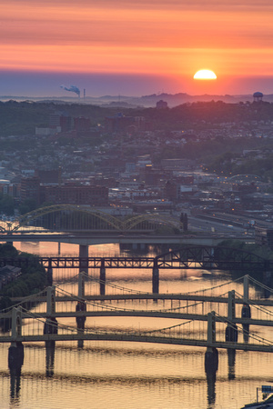 The sun rises behind the clouds at dawn above the Allegheny River in Pittsburgh