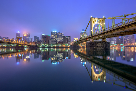 The Clemente Bridge reflects in the Allegheny on a foggy Pittsburgh morning