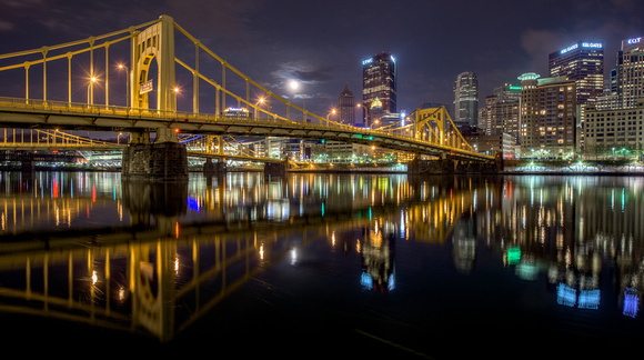 A full moon emerges from the clouds over the Andy Warhol Bridge
