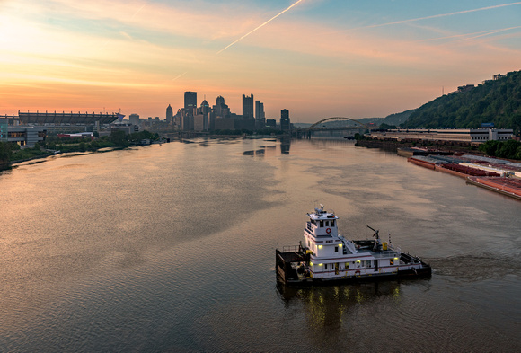 A barge turns on the Ohio River at dawn in Pittsburgh