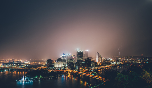 The rain is illuminated by the lights of Pittsburgh as lightning strike sin the background