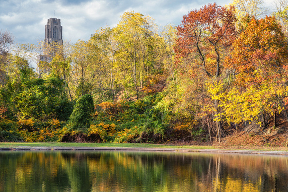 The Cathedral of Learning and fall colors reflect in Panther Hollow Lake in the fall