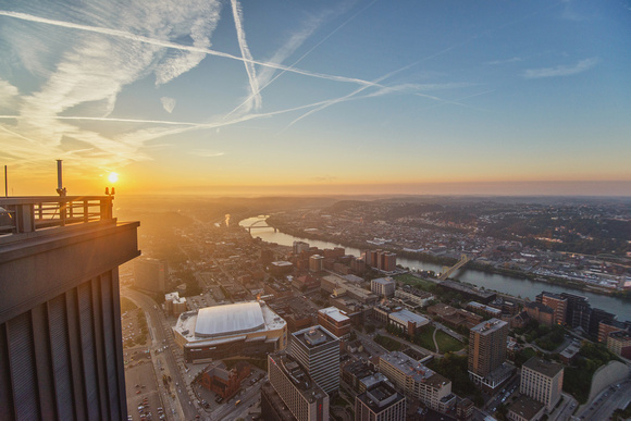 The sun rises from the roof of the Steel Building in Pittsburgh over the South Side