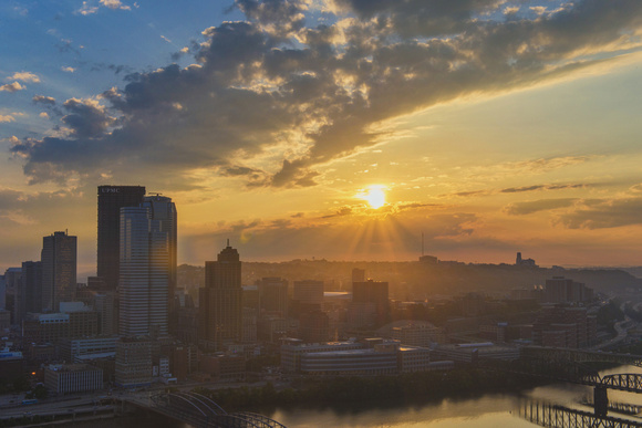 Sun flare through the clouds over Pittsburgh at dawn