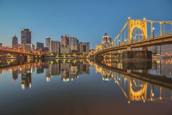 Pittsburgh and Roberto Clemente Bridge reflect in the Allegheny at dusk
