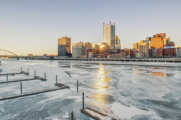 Sun reflecting off Pittsburgh skyline in the iced over Monongahela River from the Smithfield St Bridge