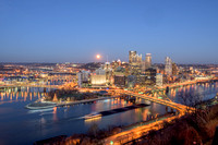 A barge passes by the full moon and PIttsburgh skyline at dusk
