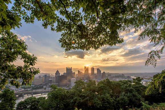 Trees on Mt. Washington frame the Pittsburgh skyline during a beautiful sunrise