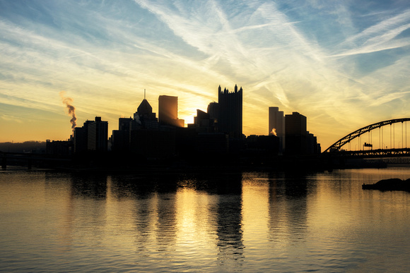 Light bursts through downtown Pittsburgh during a beautiful sunrise from the banks of the Ohio River
