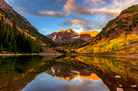 Maroon Bells glows at dawn surrounded by beautiful fall color in Colorado