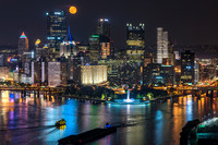 A beautiful moon rises over Pittsburgh as the city reflects in the Ohio River