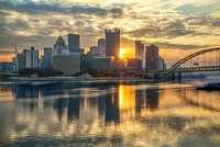 Pittsburgh lit up at dawn by the rising sun