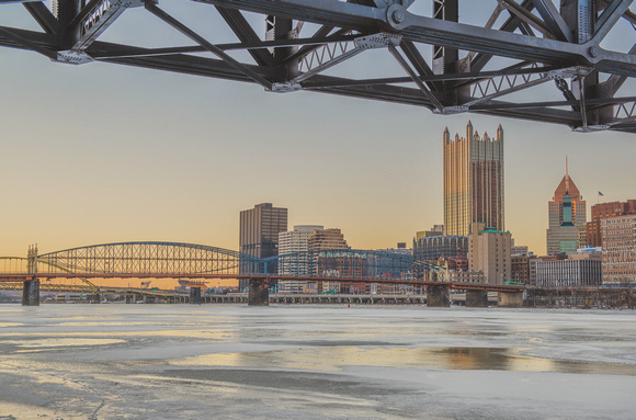 Pittsburgh framed by trolley bridge on the Monongahela River covered in ice