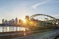 Train and Pittsburgh skyline with the sun early in the morning
