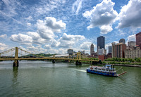 A boat from the Gateway Clipper glides under painted clouds in Pittsburgh