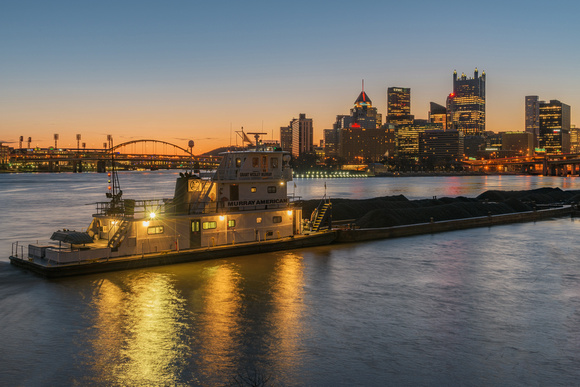A barge glows at dawn from the South Shore of Pittsburgh